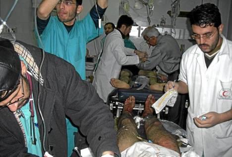 Les chirurgiens de l'hôpital Shifa opérent plusieurs patients en même temps. On notera que la stérilisation du bloc opératoire est impossible. Certains patients sont opérés dans les couloirs.