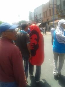 Un militant, nahjiste probablement, couvert d'un drapeau à l'effigie de la martyre Saïda Menebhi.